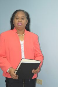Middle-aged woman of mixed ethnicity, wearing a salmon-coloured jacket, white blouse and black pants. She is holding a binder of documents, and standing in front of a blue wall.