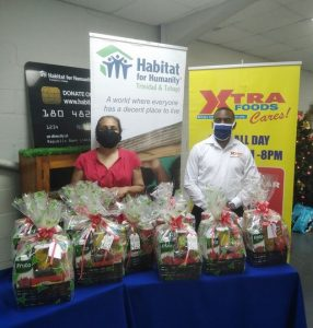 A woman in a red dress and a man in a long-sleeved white shirt stand behind a table  packed with Christmas hampers. Behind them are signs for Habitat for Humanity Trinidad and Tobago and Xtra Foods